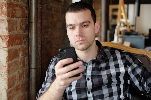 Młody hipster trzymając smartfon. pracownik biurowy na obiad rozmawia przez telefon. odnoszący sukcesy młody człowiek w ciemnej kraciastej koszuli w kawiarni prowadzi interesy. spotkanie biznesowe.