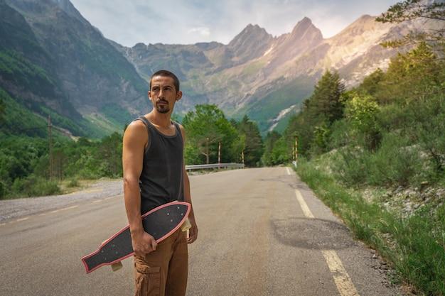 Młody hipster trzymający w dłoni fajny longboard