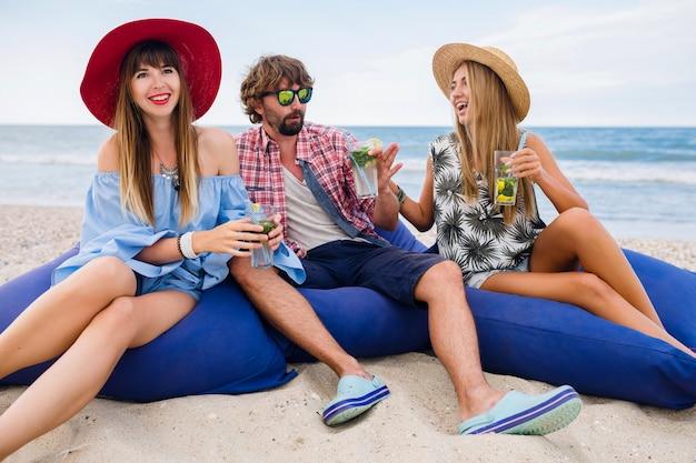Młody hipster uśmiechnięta firma szczęśliwych przyjaciół na wakacjach, siedząc w workach fasoli na imprezie na plaży, pijąc koktajl mojito
