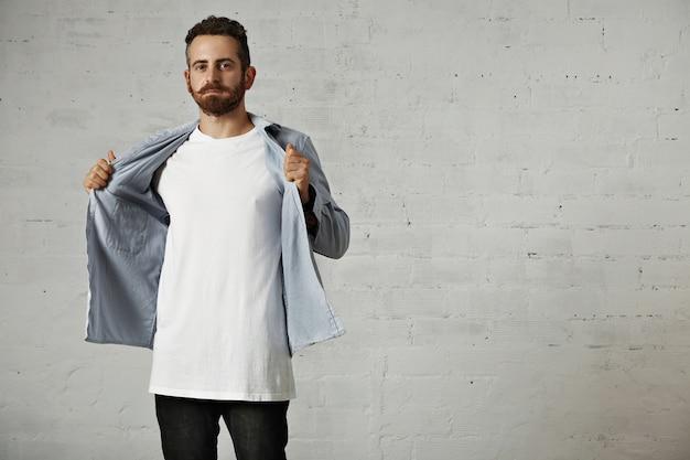 Młody hipster zdejmuje wyblakłą, niebieską dżinsową koszulę zapinaną na guziki, pokazując nieoznaczoną białą bawełnianą koszulkę na ceglanej ścianie