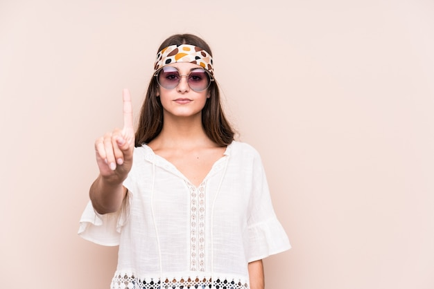 Młody hipter kaukaski kobieta na białym tle wyświetlono numer jeden z palcem.