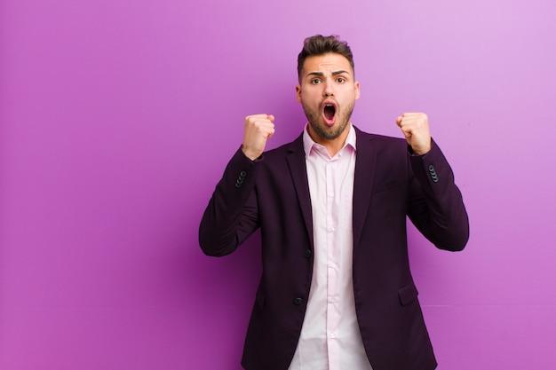 Młody hiszpan krzyczy agresywnie z gniewnym wyrazem twarzy lub zaciśniętymi pięściami, świętując sukces