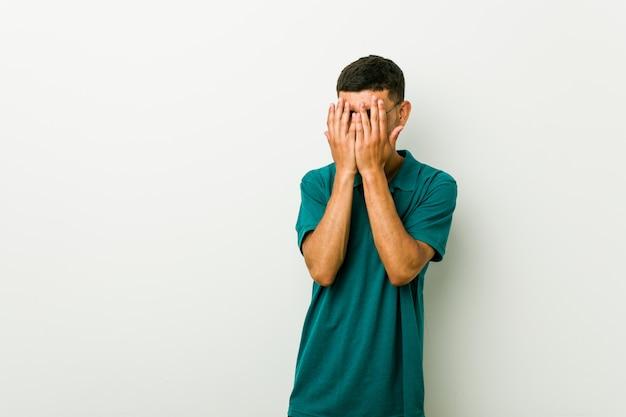 Młody hiszpan mruga przez palce przestraszony i zdenerwowany.