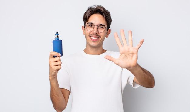 Młody hiszpanie uśmiechnięty i przyjazny, pokazując numer pięć. koncepcja parownika dymu