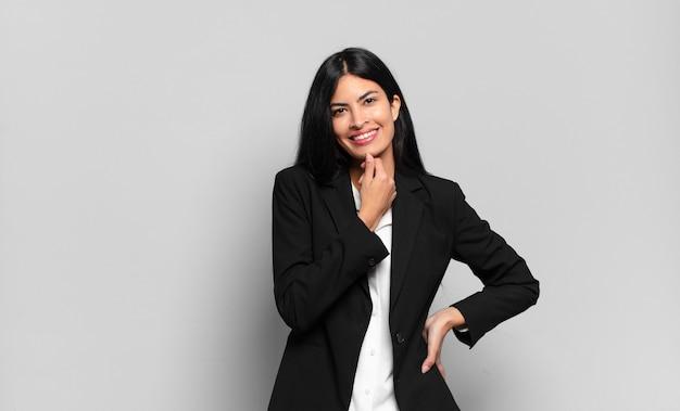 Młody hiszpanin bizneswoman szuka szczęśliwy i uśmiecha się z ręką na brodzie, zastanawia się lub zadaje pytanie, porównuje opcje