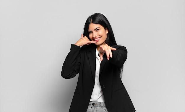 Młody hiszpanin bizneswoman uśmiecha się radośnie i wskazując podczas nawiązywania połączenia z tobą później gestem, rozmawiając przez telefon