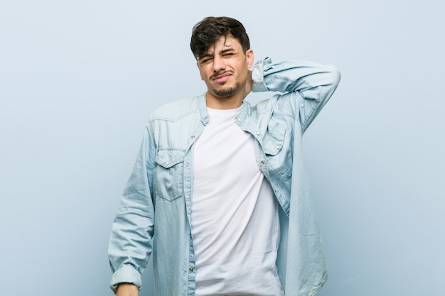 Młody hiszpanin fajny człowiek cierpi ból szyi z powodu siedzącego trybu życia.