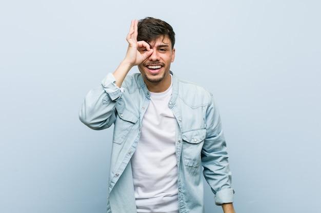 Młody hiszpanin fajny człowiek podekscytowany, trzymając ok na oku