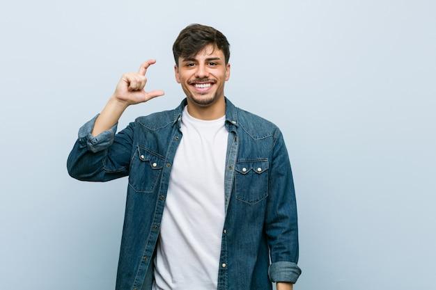 Młody hiszpanin fajny człowiek trzyma coś z palcami wskazującymi, uśmiechnięty i pewny siebie.