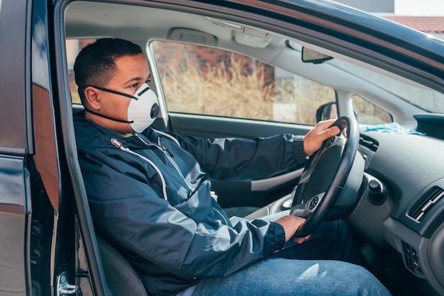 Młody hiszpanin jest sam w samochodzie, nosi maskę ochronną