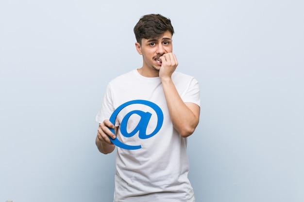 Młody hiszpanin mężczyzna trzyma ikonę obgryzanie paznokci, nerwowy i bardzo niespokojny.