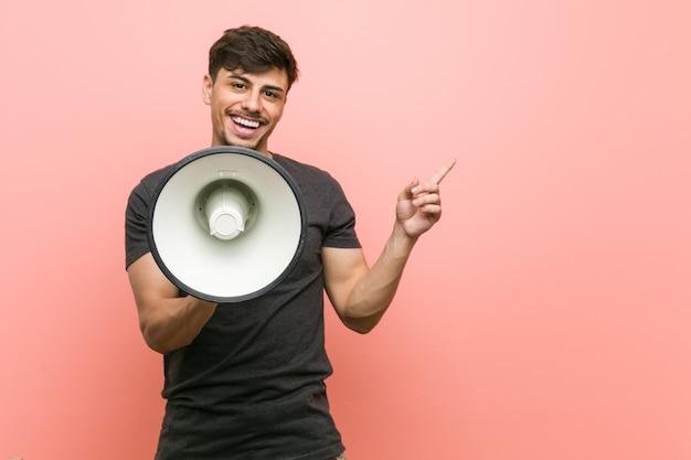 Młody hiszpanin mężczyzna trzyma megafon uśmiecha się wesoło wskazując palcem wskazującym daleko.