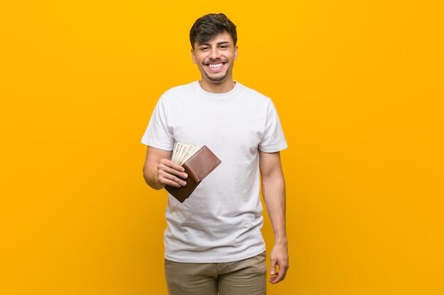 Młody hiszpanin mężczyzna trzyma portfel szczęśliwy, uśmiechnięty i wesoły.