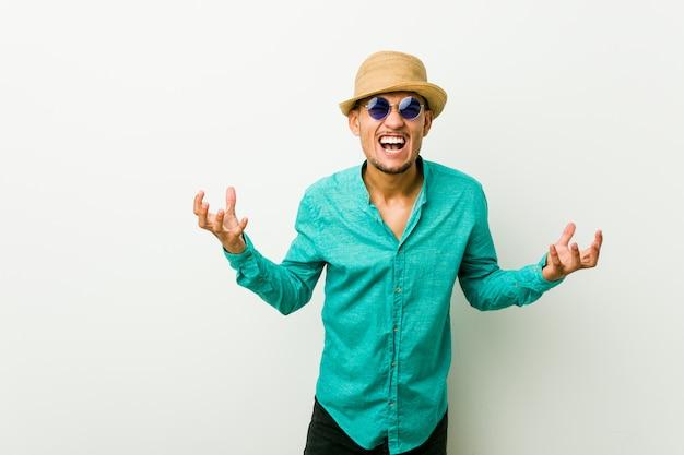 Młody hiszpanin mężczyzna ubrany w letnie ubrania krzyczy z wściekłości.