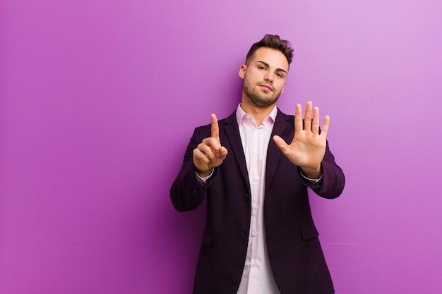 Młody hiszpanin mężczyzna uśmiecha się i wygląda przyjaźnie, pokazuje numer sześć lub szósty ręką do przodu, odliczając