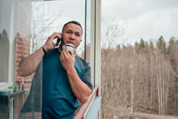 Młody hiszpanin mężczyzna w masce patrząc z balkonu i rozmawia z przyjaciółmi przez telefon