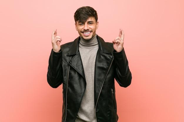 Młody hiszpanin mężczyzna w skórzanej kurtce skrzyżowane palce za szczęście
