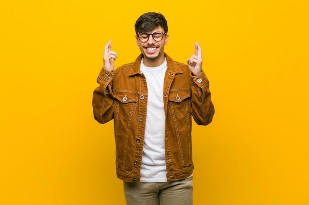 Młody hiszpanin przypadkowy mężczyzna krzyżuje palce za mieć szczęście