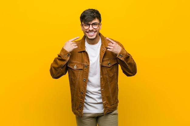 Młody hiszpanin przypadkowy mężczyzna uśmiecha się, wskazując palcami na usta