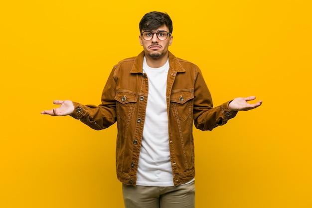 Młody hiszpanin przypadkowy mężczyzna wątpi i wzrusza ramionami w pytającym geście.