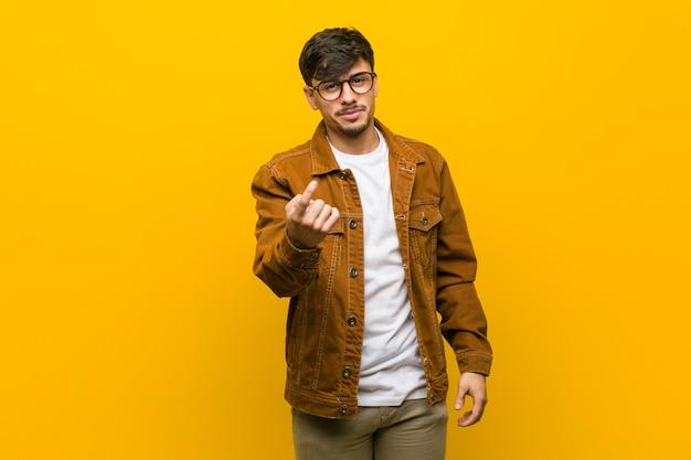 Młody hiszpanin przypadkowy mężczyzna wskazujący palcem na ciebie, jakby zapraszający, podejdź bliżej.