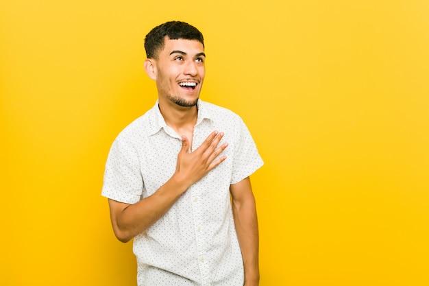 Młody hiszpanin śmieje się głośno, trzymając rękę na piersi.