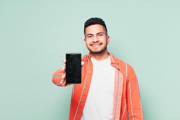 Młody hiszpanin szczęśliwy wyraz twarzy i trzymający telefon komórkowy