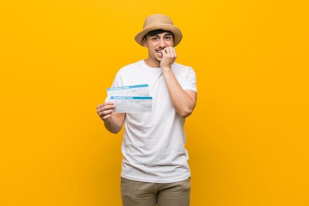 Młody hiszpanin trzyma bilety lotnicze gryząc paznokcie, nerwowy i bardzo niespokojny.