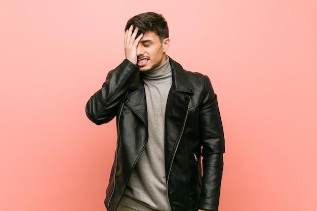 Młody hiszpanin w skórzanej kurtce, zapominając o czymś, uderzając dłonią w czoło i zamykając oczy.