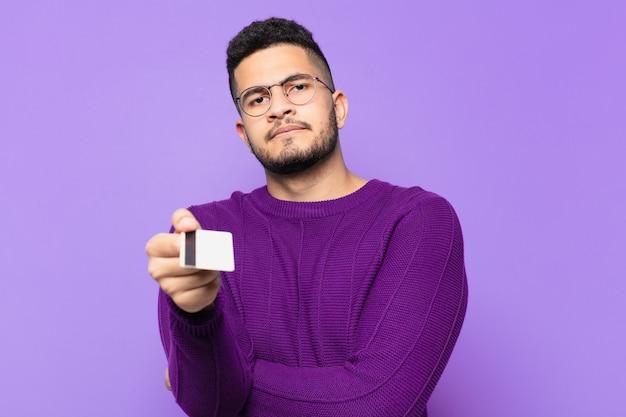 Młody hiszpanin zły wyraz twarzy i trzymający kartę kredytową