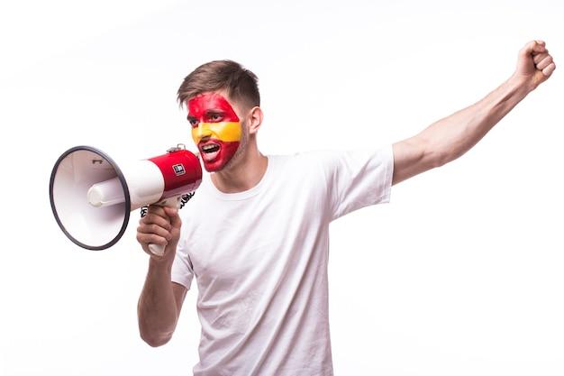 Młody hiszpański człowiek fan piłki nożnej z megafonem na białym tle na białej ścianie