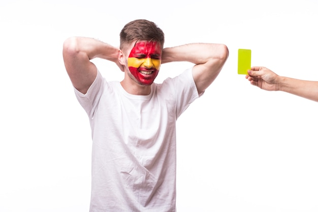 Młody hiszpański człowiek fan piłki nożnej z żółtą kartką na białym tle na białej ścianie