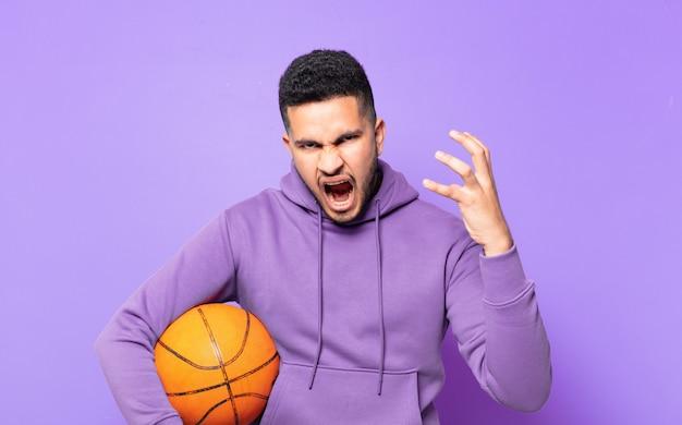 Młody hiszpański sportowiec mężczyzna zły wyraz twarzy i trzymający piłkę do koszykówki