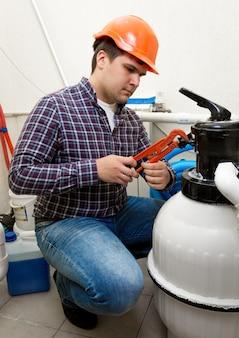 Młody hydraulik instalujący manometr na beczce wysokociśnieniowej