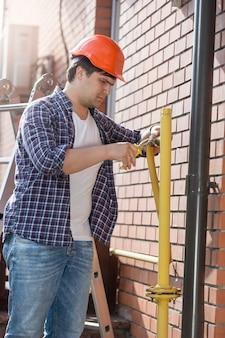 Młody hydraulik w kasku naprawiający rury w domu