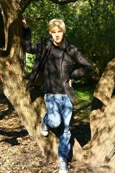 Młody i atrakcyjny facet pozuje w parku