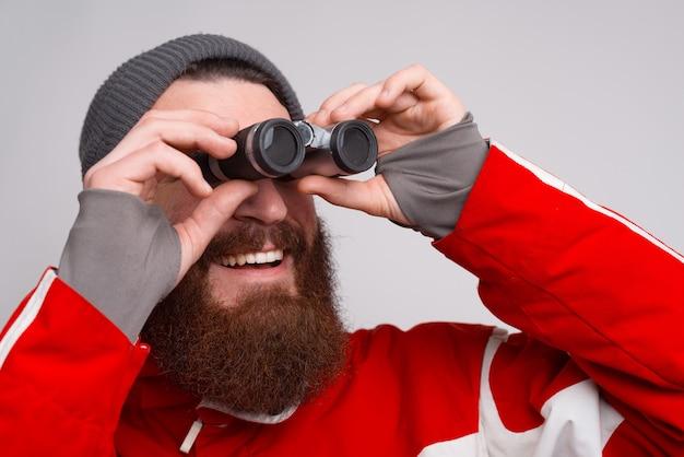 Młody i brodaty wspinacz uśmiecha się i patrzy przez lornetkę. mężczyzna w strojach zimowych czeka.