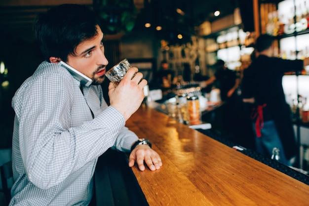 Młody i ciemnowłosy facet siedzący przy stoisku kelnera w klubie i popijający alkohol. również rozmawia przez telefon i próbuje jednocześnie pić. barman stoi daleko od niego.