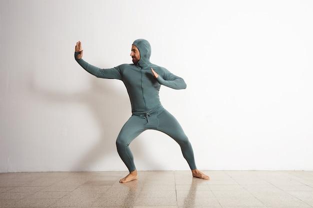 Młody i dopasowany, brodaty sportowiec, ubrany w zimowy snowboardowy kombinezon termiczny i dobrze się bawi, zachowując się jak ninja