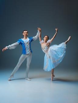 Młody i pełen wdzięku tancerzy baletowych jako postaci bajki kopciuszek na tle studio. sztuka, ruch, akcja, elastyczność, koncepcja inspiracji. elastyczni tancerze baletu kaukaskiego pozują, tańczą.