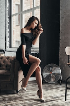 Młody i piękny. atrakcyjna młoda kobieta w eleganckiej czarnej sukni trzymająca rękę we włosach siedząc w fotelu