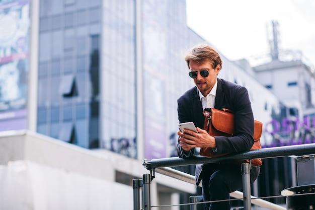 Młody i przystojny biznesmen pracuje w podróży na swoim telefonie