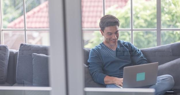 Młody i przystojny biznesmen rasy kaukaskiej ubrany dorywczo tkaniny siedzi szczęśliwie na kanapie i za pomocą laptopa notebook komunikować się ze światem zewnętrznym. pomysł na pracę z domu koncepcja