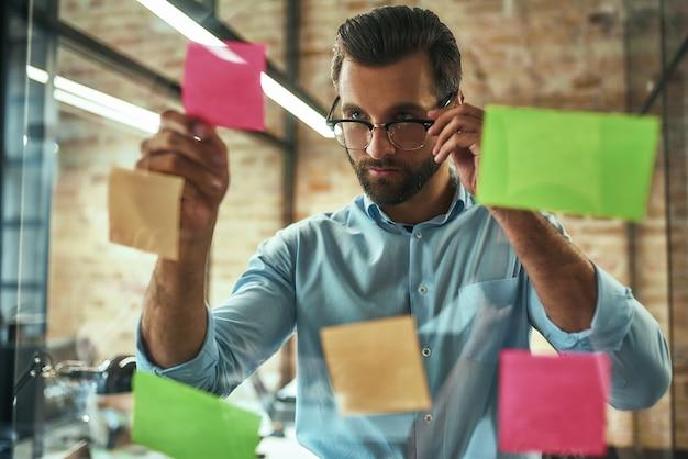 Młody i przystojny biznesmen w okularach planuje proces pracy i używa kolorowych naklejek