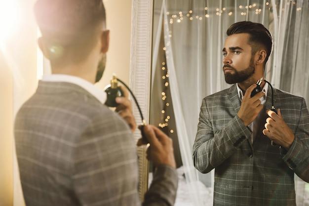 Młody i przystojny brodaty mężczyzna używa rozpylacza z perfumami