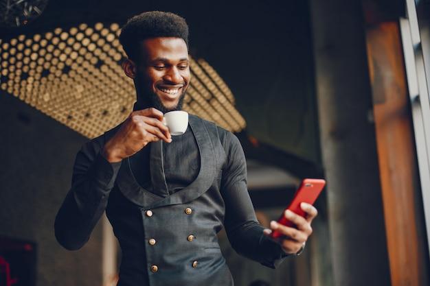 Młody i przystojny ciemnoskóry chłopak w czarnym garniturze stojącym w kawiarni