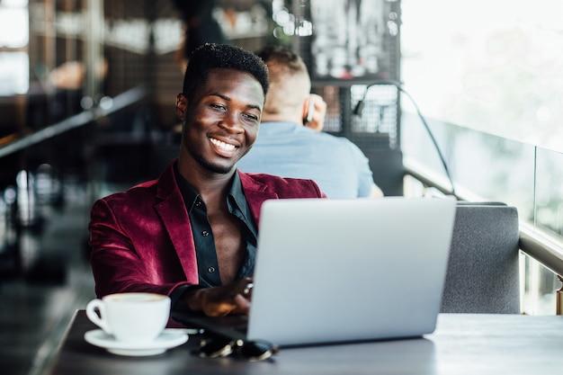 Młody i przystojny ciemnoskóry chłopak w garniturze siedzi w kawiarni i laptopie.