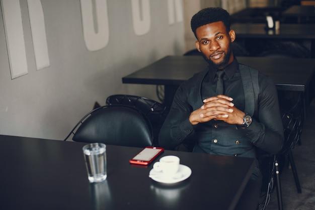 Młody i przystojny ciemnoskóry chłopiec w czarnym garniturze siedząc w kawiarni