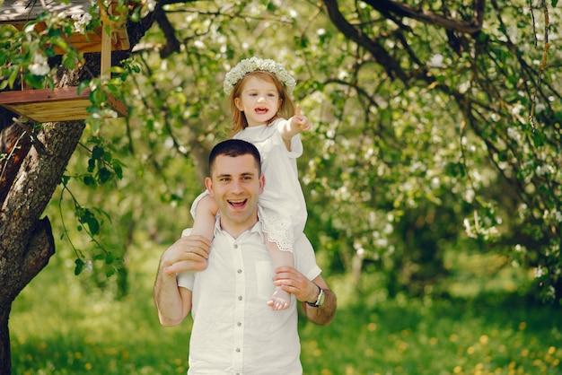 Młody i przystojny ojciec bawi się ze swoją córeczką w letnim parku