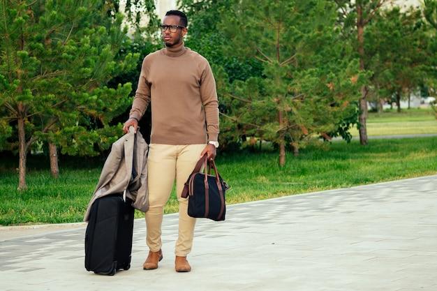 Młody i przystojny stylowy model afro-amerykański mężczyzna w stylowym garniturze w letnim parku latynoski hiszpański biznesmen czarny facet bogaty turysta idący z walizką na lotnisko na konferencję